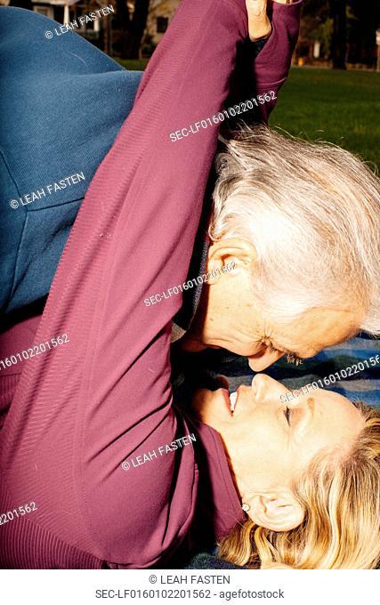 Senior couple rubbing noses in park