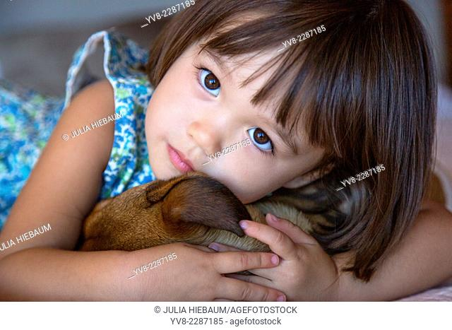 Toddler girl holding her puppy dog