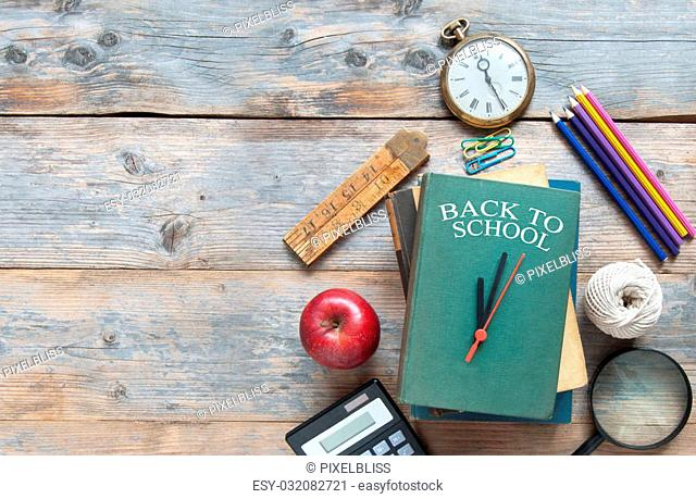 Book with clock hands with stationery accessories on a wooden and space for text