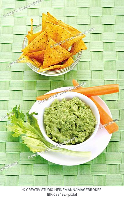 Nachos and avocado dip (guacamole) garnished with carrots and celery