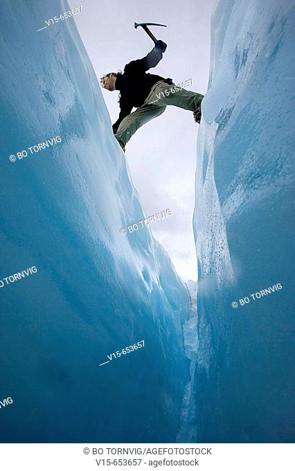 Mountaineer jumbing a crevasse on a glaicier