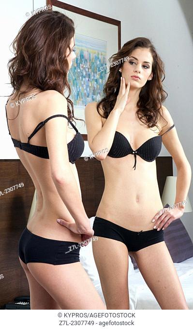 Woman in underwear looking in mirror