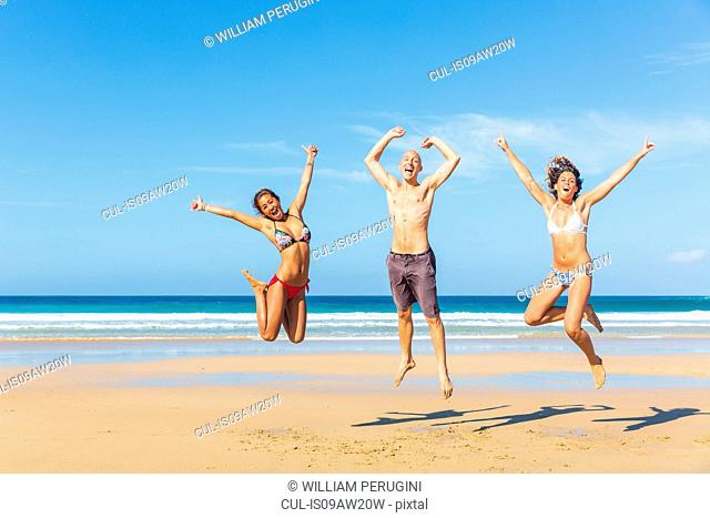 Man and two young women wearing swimwear jumping on beach, El Cotillo, Fuerteventura, Spain