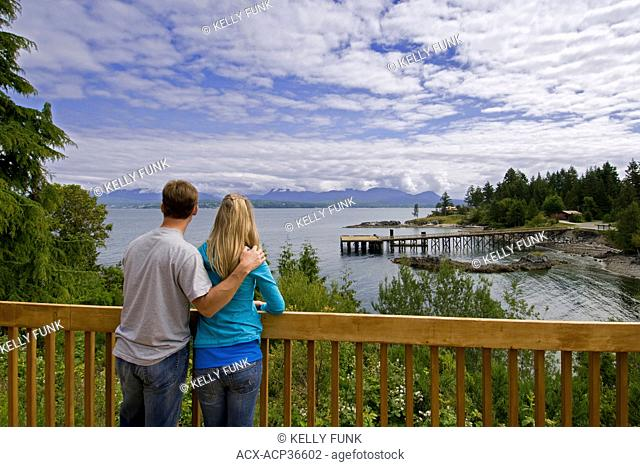 A young couple checks out the view of Texada island from a bed and breakfast on the upper Sunshine coast, Gulf islands region, British Columbia, Canada