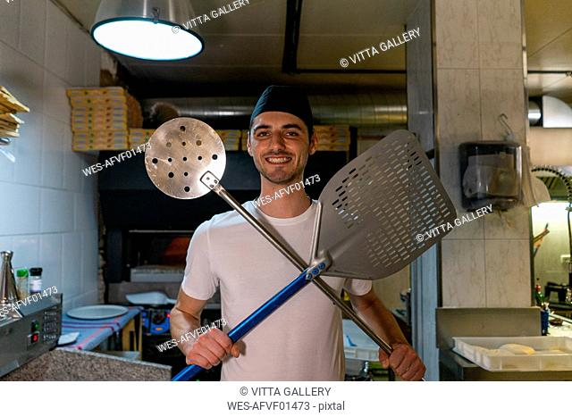 Portrait of smiling pizza baker holding pizza peel and big skimmer in kitchen
