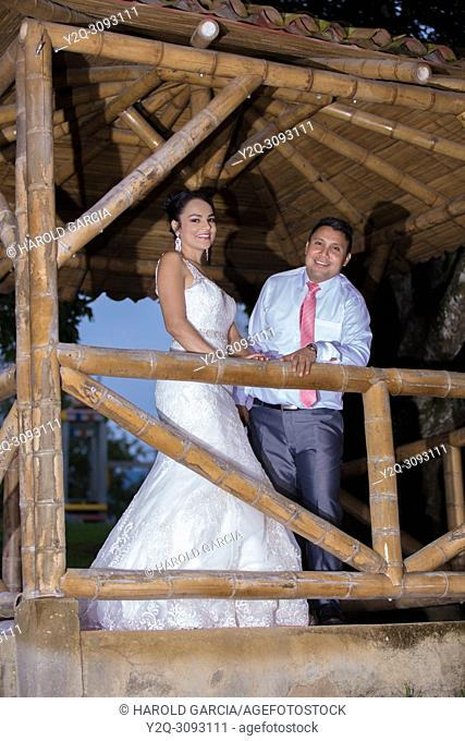 Wedding couple posing outdoors in a bamboo gazebo