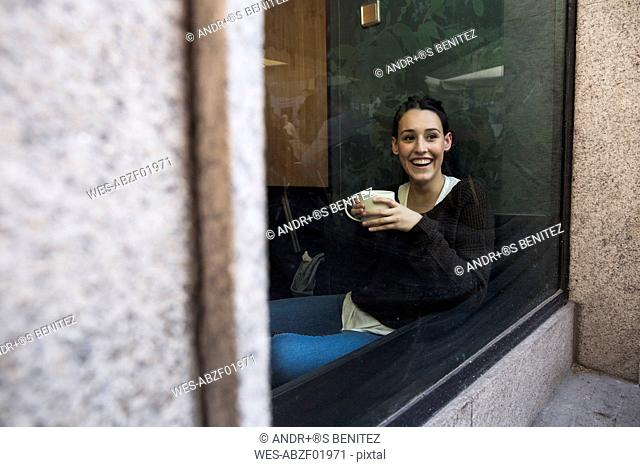 Portrait of smiling woman with cup of coffee sitting behind windowpane in a coffee shop