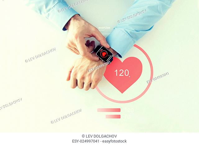 business, technology, health care, application and people concept - close up of male hands setting smart watch with red heart icon screen