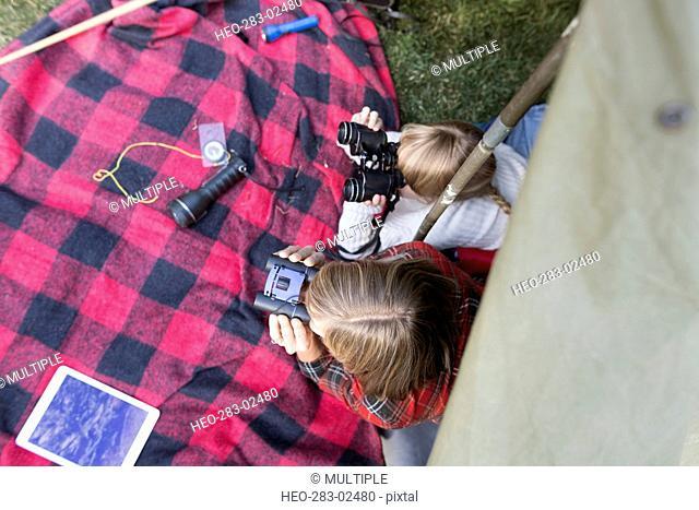 Overhead view sisters using binoculars in tent