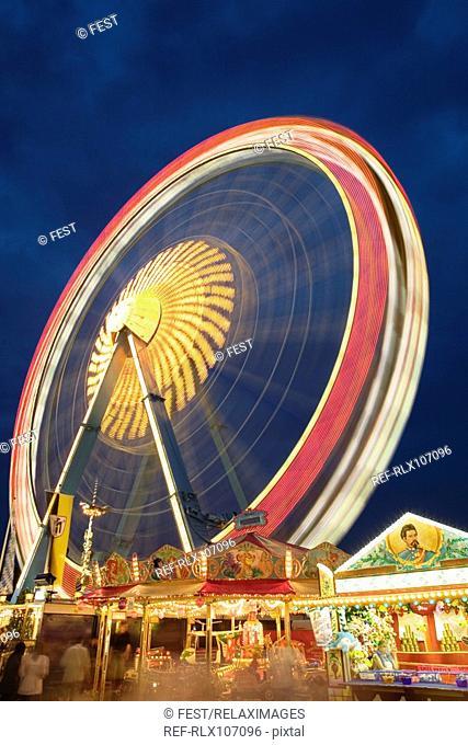 Illuminated Ferris wheel at night, Oktoberfest beer festival, Munich, Germany