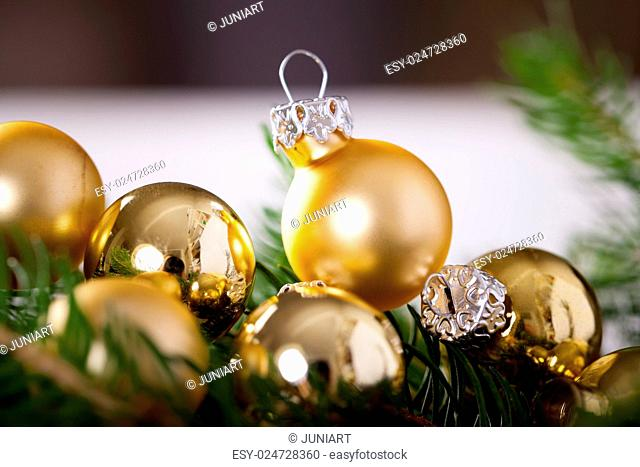 Golden Christmas decoration background with a variety of gold baubles and balls of different sizes and textures nestling on a branch of natural evergreen pine