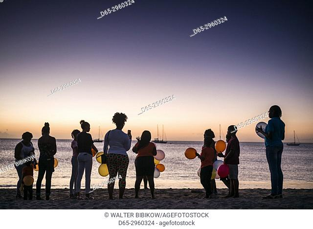 St. Kitts and Nevis, Nevis, Pinneys Beach, silhouettes of people with balloons, dusk