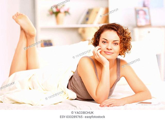 Life is good. Pretty charming upbeat girl holding hand near her face and lying in bed while relaxing