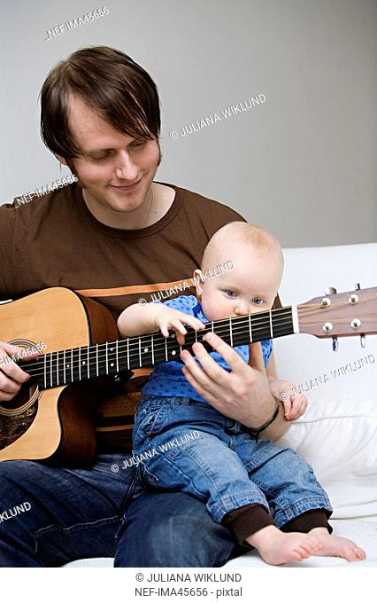 A man and a baby playing guitar