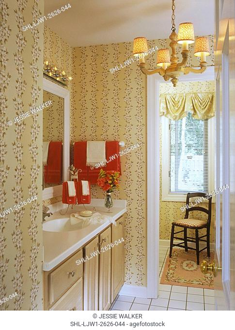 BATHROOMS: Quest bath, view towards vanity sink area and doorway. Floral wallpaper in soft pinks and creams, white ceramic tile floor, antique chandelier