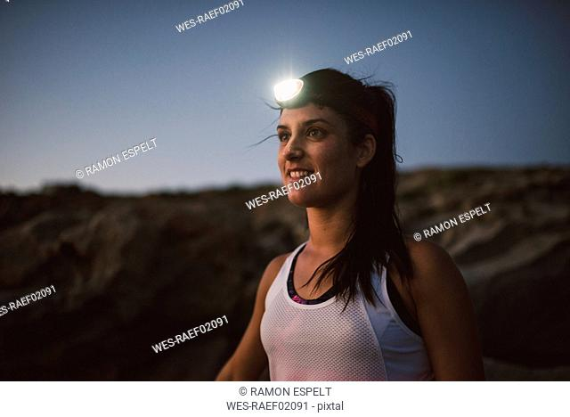 Sportive woman with headlamp in the evening