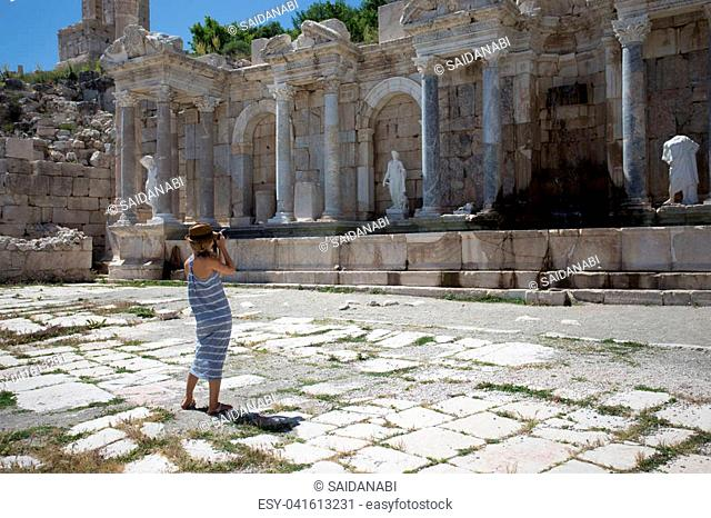 Woman traveller wearing long summer dress and hat photographing agora with marble columns and statues at ancient city of Sagalassos