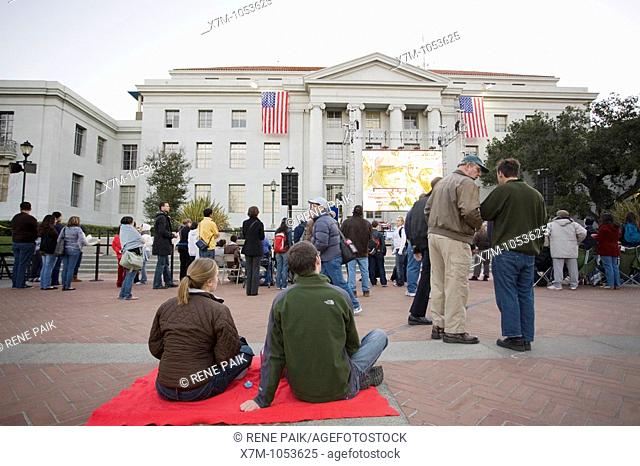 A couple sit on a blanket waiting to watch the inauguration of Barack Obama on the jumbotron at the University of California at Berkeley