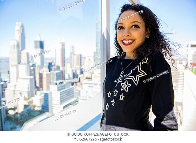 New York, USA. Attractive, Hispanic woman overlooking Down Town Manhattan from the 58th floor of her apartment building