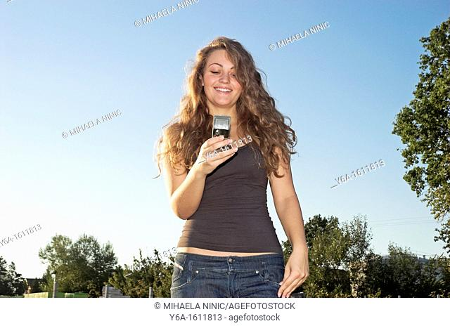 Smiling young woman in park using cell phone