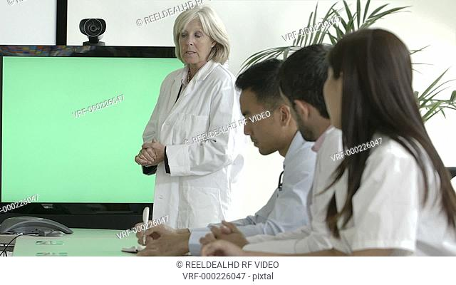 MS Female doctor explaining with projection equipment in meeting room
