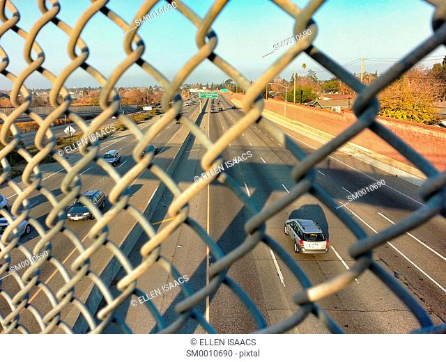 Cars driving on a highway as seen through a chain link fence from an overpass in California on a weekend day with light traffic
