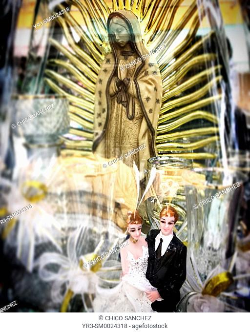 A just married couple and an image of Our Lady of Guadalupe decorate a wedding shop in Puebla, Mexico