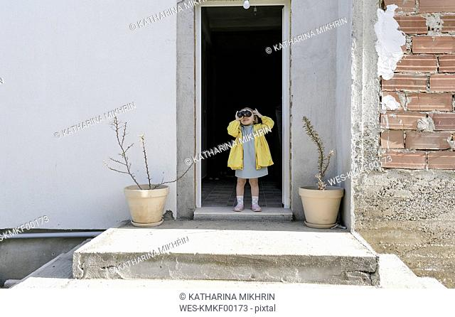 Little girl standing at house entrace using binoculars