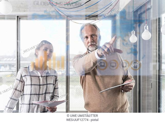 Casual mature businessman and young woman discussing data at glass pane in office