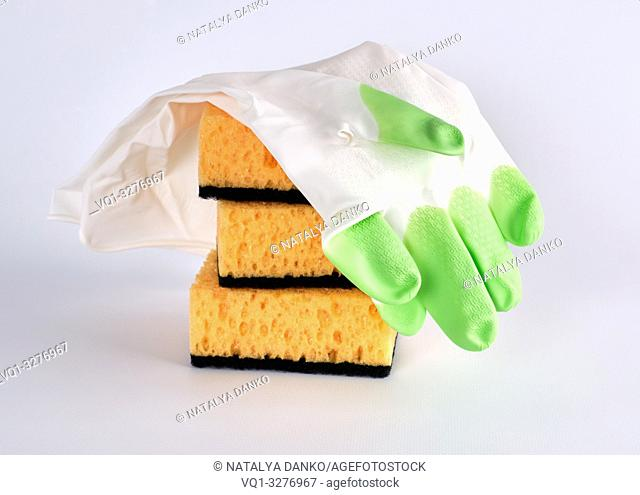 stack of yellow kitchen sponges for washing dishes and gloves on a white background