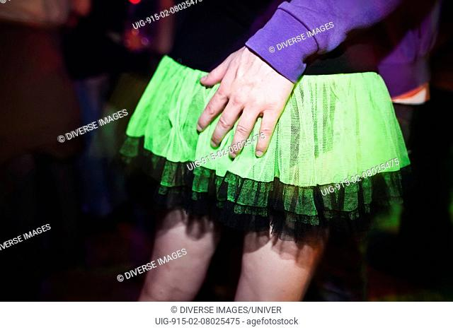 Close-up of party-goers bright green skirt. Bang Face weekender, Camber Sands, Sussex, UK. April 2010