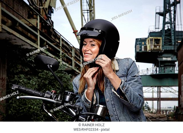 Smiling young woman putting on motorcycle helmet
