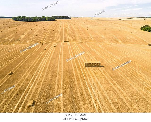 Aerial landscape of harvested summer farm wheat and barley fields and straw bales