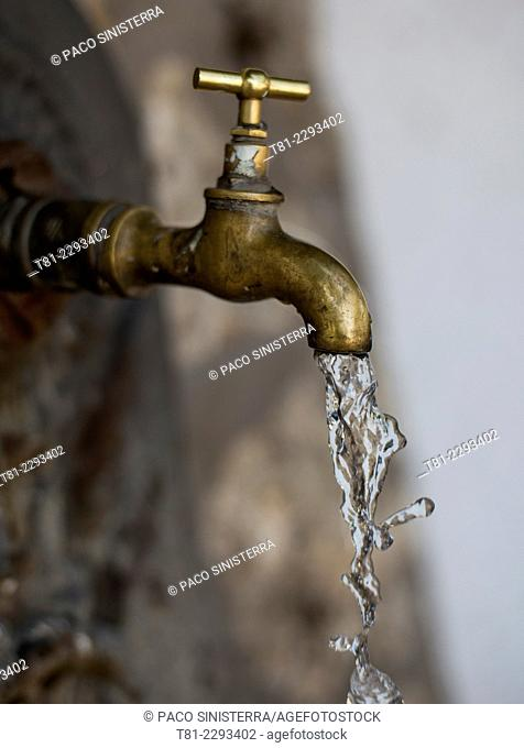 Water coming out of an ancient basin faucet, Spain
