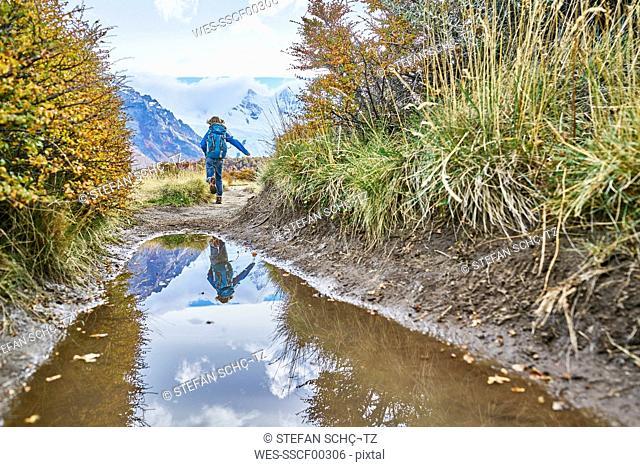 Argentina, Patagonia, El Chalten, boy running at puddle at Cerro Torre in Los Glaciares National park