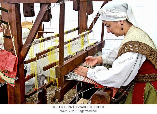 Woman wearing traditional Asturias dress at old loom, Aviles, Asturias, Spain