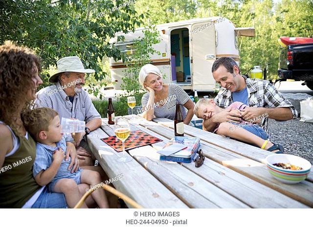 Multi-generation family bonding at campsite picnic table