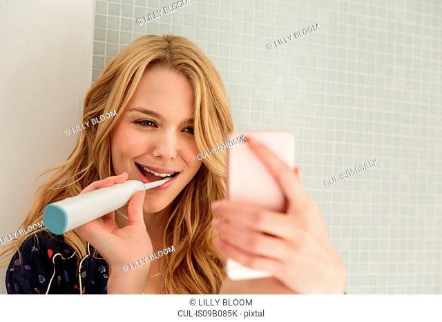 Woman brushing teeth, taking selfie
