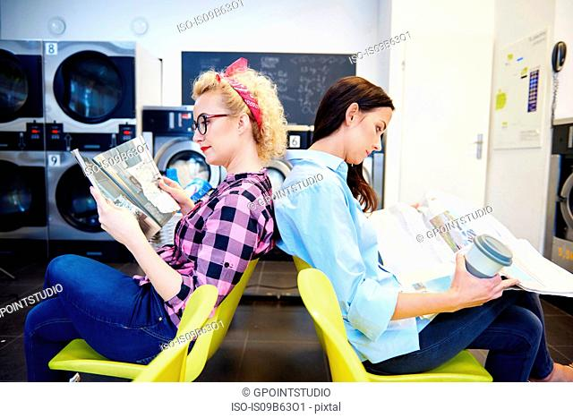 Two women reading newspapers back to back in laundrette