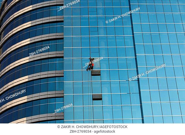 DHAKA, BANGLADESH - DECEMBER 03 : A labor clean the glass-wall of a high-rise building in Dhaka, Bangladesh on December 03, 2016
