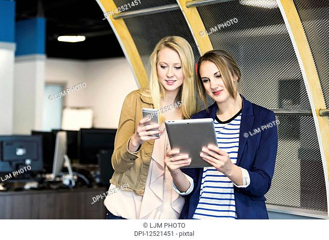 Two beautiful young millennial business women using technology in the workplace; Sherwood Park, Alberta, Canada