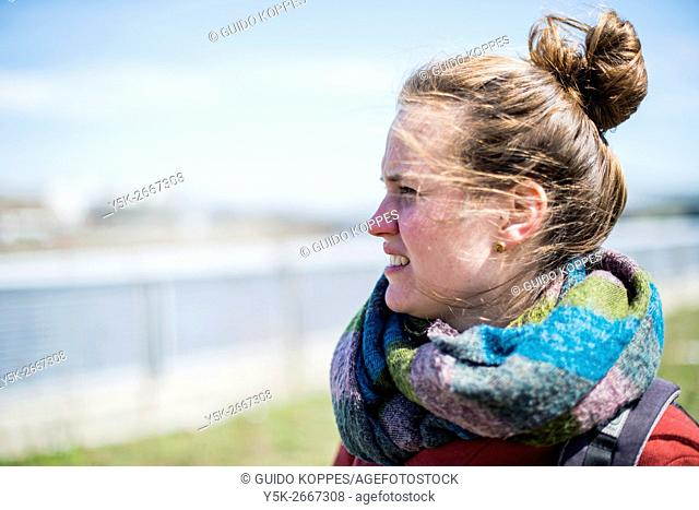 Newark, New Jersey, USA. Young brunette woman overlooking the Passaic River