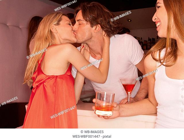 Germany, Stuttgart, Couple kissing in nightclub, woman smiling at them