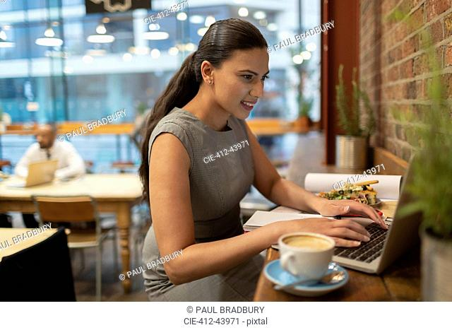 Businesswoman working at laptop in cafe