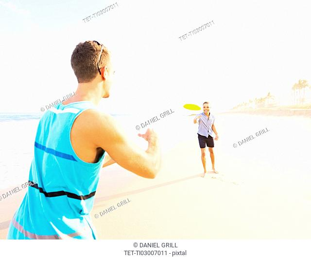 Young men playing plastic disc on beach