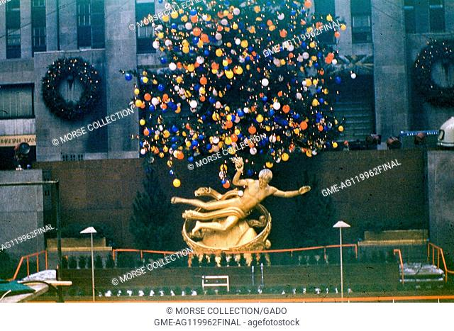 View of Prometheus, the gilded bronze statue by sculptor Paul Manship, reclining beneath the Christmas tree at Rockefeller Center Plaza, midtown Manhattan