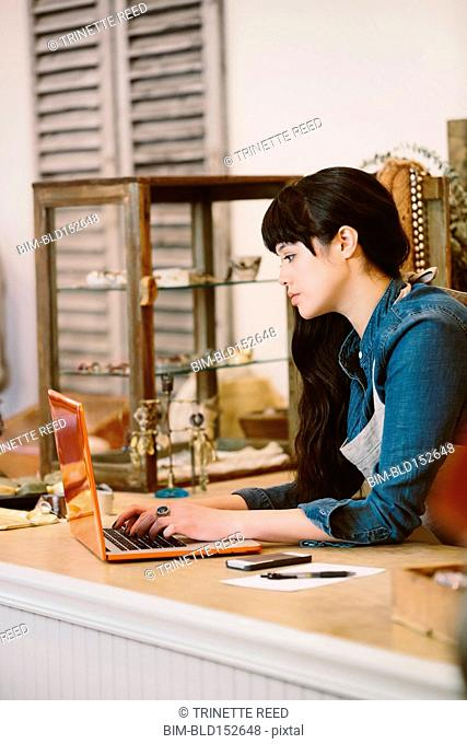 Mixed race employee using laptop in clothing store