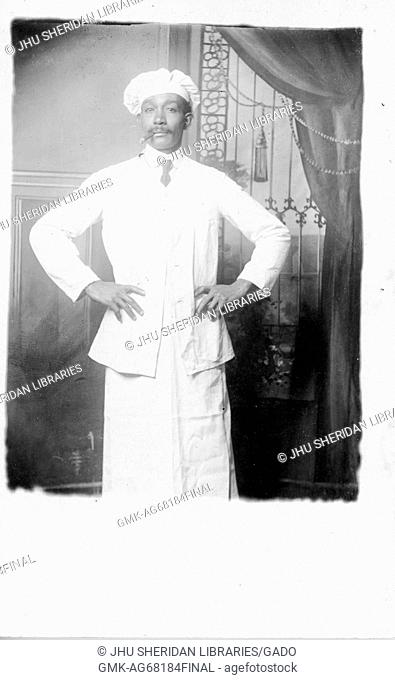 Three quarter length portrait of mature African American man, wearing light outfit, light shirt, dark tie and chef hat, holding cigar in mouth