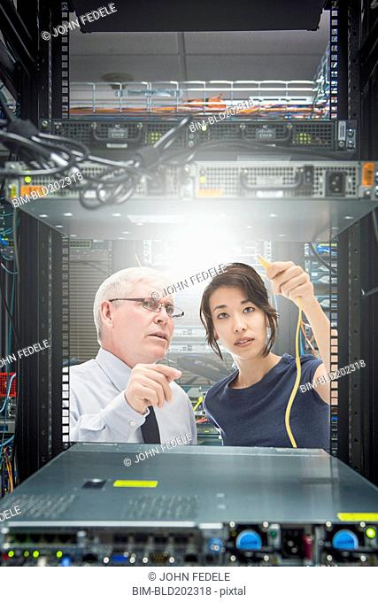 Business people working in server room