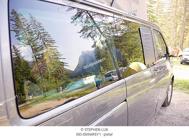 Camper van parked in forest campsite, Lake Toblach, Dolomites, South Tyrol, Italy